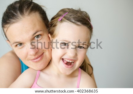 Mother and daughter embracing, smiling, being affectionate, happy and loving. Parenthood, childhood, happiness and family life concept. Grey seamless background. - stock photo