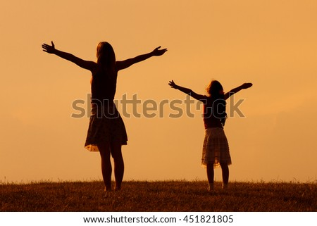Mother and daughter enjoy in sunset together.Greeting the sunset - stock photo