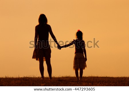 Mother and daughter enjoy watching sunset together.Precious family moments - stock photo
