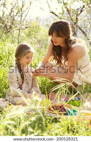 Mother and daughter enjoying a picnic together in a green field with flowers, eating strawberries with mom crouching to help the young girl. Family activities and healthy eating lifestyle, outdoors. - stock photo