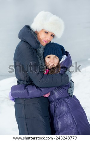 Mother and daughter enjoying beautiful winter day outdoors - stock photo