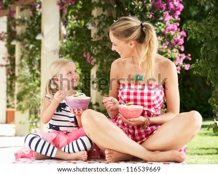 Mother And Daughter Enjoying Breakfast Cereal Outdoors Together - stock photo