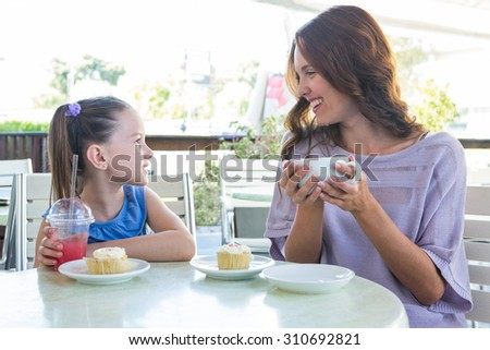 Mother and daughter enjoying cakes at cafe terrace on a sunny day - stock photo