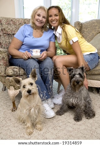 mother and daughter enjoying coffee with their dogs