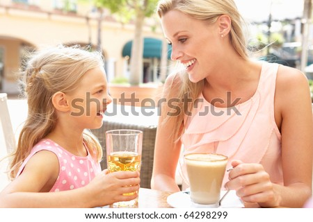 Mother And Daughter Enjoying Cup Of Coffee And Juice In Cafe Together - stock photo