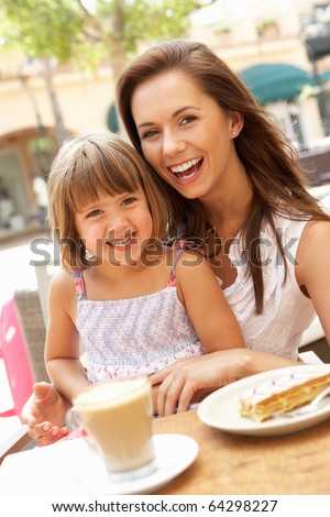 Mother And Daughter Enjoying Cup Of Coffee And Piece Of Cake In Cafe - stock photo