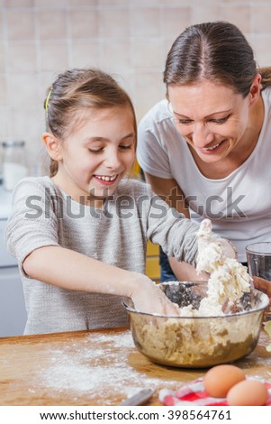 Mother and daughter enjoying making dough - stock photo