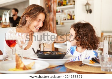 Mother And Daughter Enjoying Meal In Restaurant - stock photo