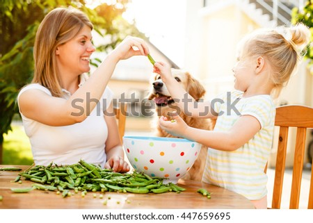 Mother and daughter enjoying outside and peeling peas off. - stock photo