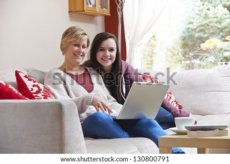 Mother and daughter enjoying surfing on the net while relaxing at home with coffee - stock photo