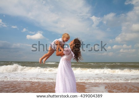 mother and daughter enjoying time at sandy beach - stock photo