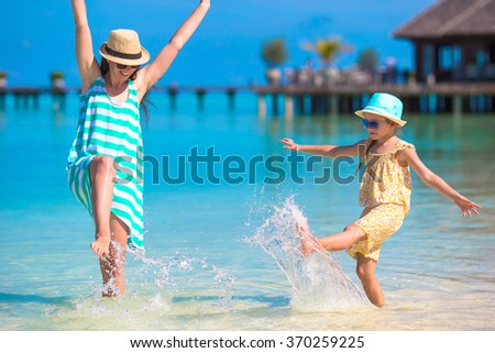 Mother and daughter enjoying time at tropical beach - stock photo