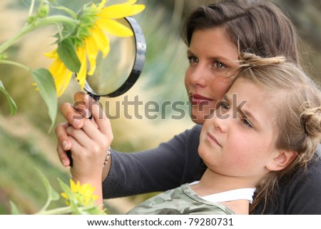 Mother and daughter examining a sunflower through a magnifying glass - stock photo