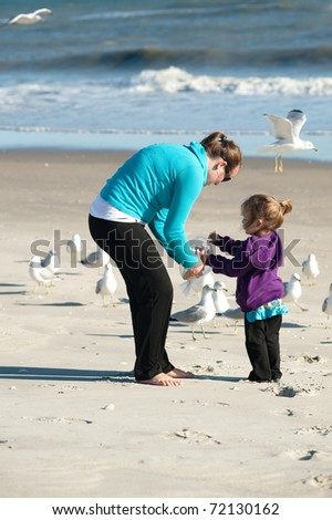 mother and daughter feeding seagulls at the beach - stock photo