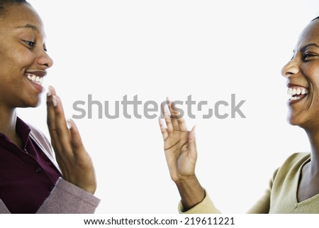 Mother and daughter giving each other high five - stock photo