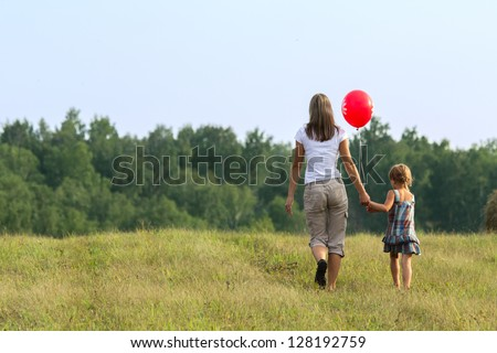 Mother and daughter going to mowed grass. View from back. - stock photo