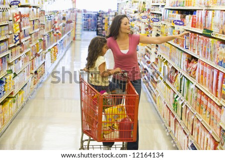 Mother and daughter grocery shopping in supermarket - stock photo