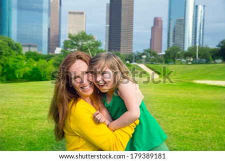 Mother and daughter happy hug laughing in park at city modern skyline background - stock photo