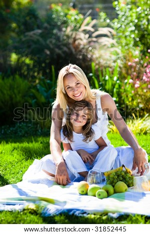 Mother and daughter having a picnic in  a park - stock photo