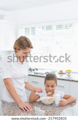 Mother and daughter having breakfast at home in kitchen - stock photo