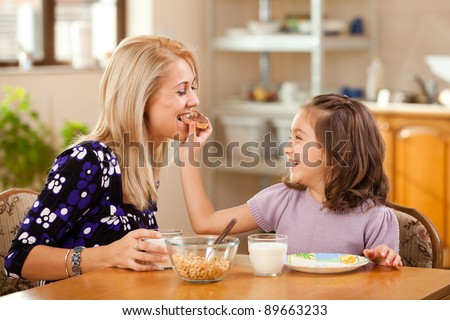mother and daughter having breakfast: eating chocolate cream on a slice of bread