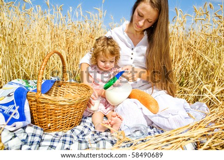 Mother and daughter having breakfast in field - stock photo