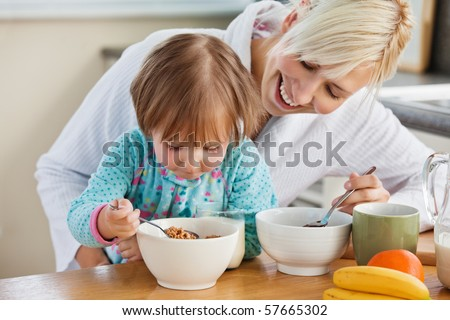 Mother and daughter having breakfast in kitchen - stock photo