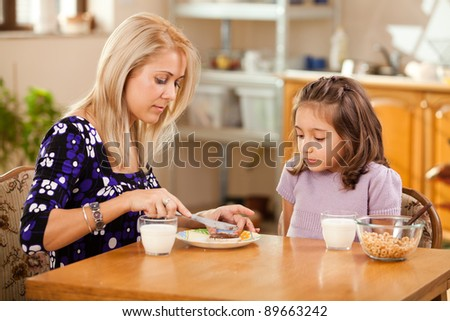 mother and daughter having breakfast: spreading chocolate cream on a slice of bread - stock photo