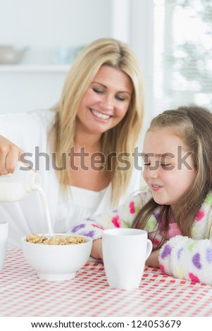 Mother and daughter having cereal at breakfast in kitchen