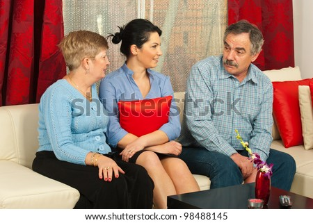 Mother and daughter having conversation with sad father in their home - stock photo