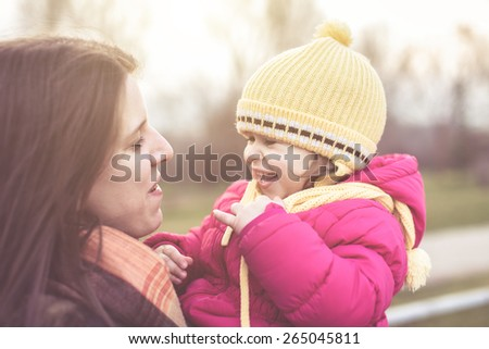 Mother and daughter having fun and  looking at each other. Cute kid in jacket hugging mom . Happy smiling people outdoor . Love between child and parent. Family outdoor activity. - stock photo