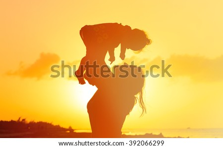 mother and daughter having fun at sunset - stock photo