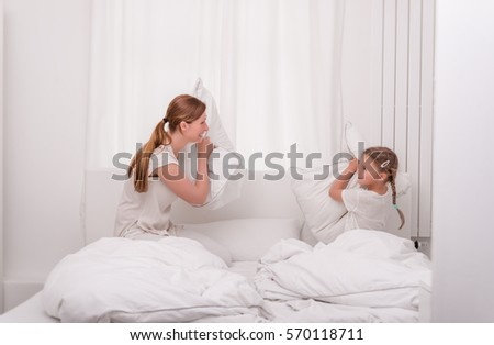 mother and daughter having fun fighting bed