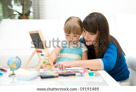 mother and daughter having fun in kindergarten - stock photo