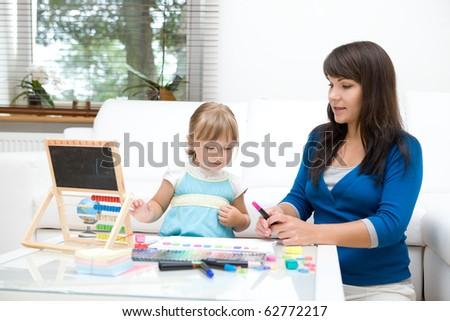mother and daughter having fun in kindergarten - stock photo
