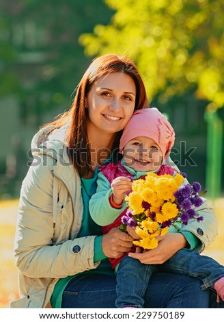 Mother and daughter having fun in the autumn park among the falling leaves. - stock photo