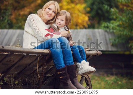 Mother and daughter having fun in the autumn park on cart