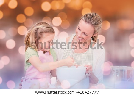 Mother and daughter having fun in the kitchen against glowing background - stock photo