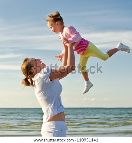 Mother and daughter having fun near the sea
