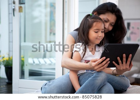 Mother and Daughter having fun on a digital tablet in a home interior - stock photo