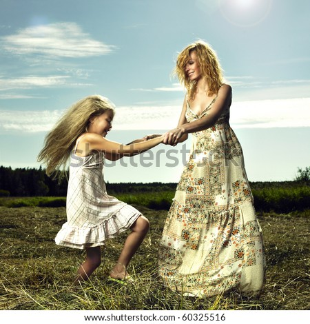 Mother and daughter having fun on field - stock photo