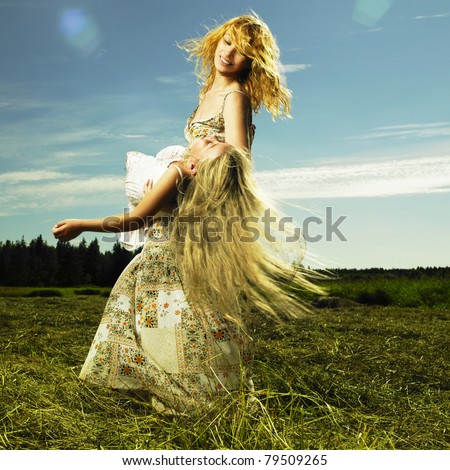 Mother and daughter having fun on field. Summer day - stock photo