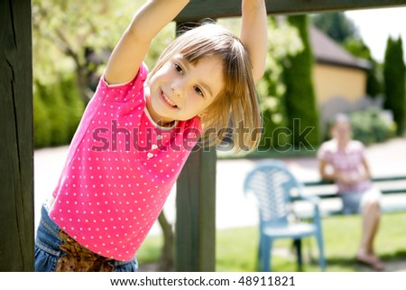 Mother and daughter having fun on playground - stock photo