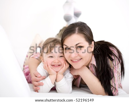 mother and daughter having fun on sofa - stock photo