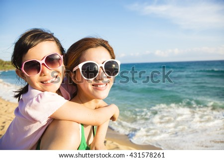 Mother and Daughter having fun on the beach - stock photo