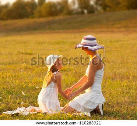 Mother and daughter having fun on the meadow on sunny summer day. - stock photo