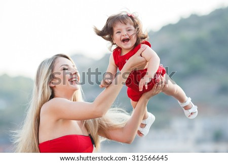 Mother and daughter having fun on wooden bridge by the sea. Happy Family by the Sea. mother playin with baby girl. Woman with child in marine sea style - stock photo