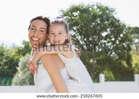 Mother and daughter having fun outside in the garden - stock photo