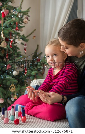Mother and daughter having fun painting finger nails on xmas day