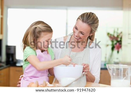 Mother and daughter having fun together in the kitchen - stock photo